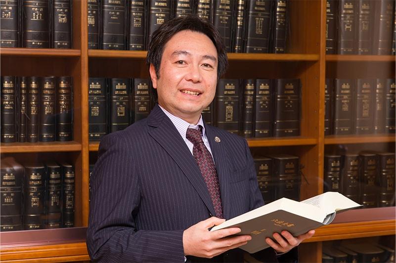 六法全書が並ぶ本棚の前に立つ朝日中央綜合法律事務所の弁護士